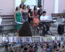 参加者の前で歌う小笠原さんと片山さん、ギリシャの参加者たち